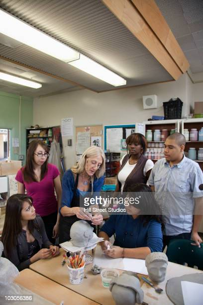 teacher demonstrating sculpting to students - gardena california stock pictures, royalty-free photos & images