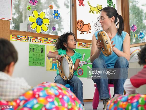 teacher demonstrating tambourine playing - tambourine ストックフォトと画像