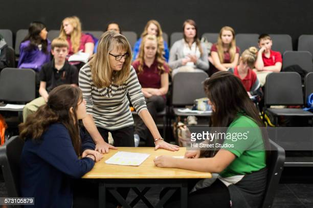 Teacher directing students with scripts in drama class