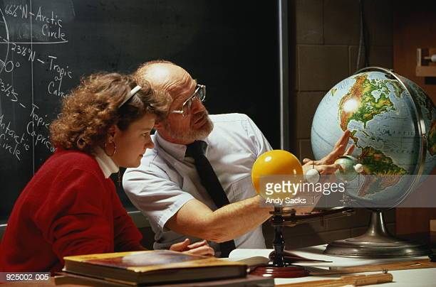 Teacher discussing model of solar system with student