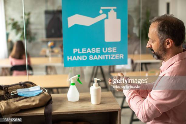 teacher disinfecting hands with hand sanitizer before entering classroom - reopening stock pictures, royalty-free photos & images