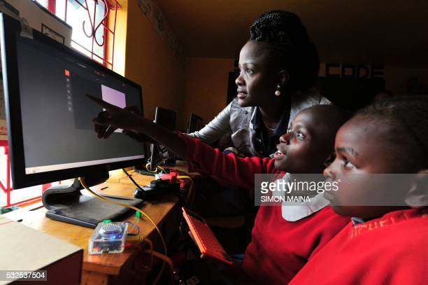 Teacher Dorothy Atieno shows pupils of Kibera School for Girls how to use computers at Nairobi on May 19 2016 Kibera School for Girls offers free...