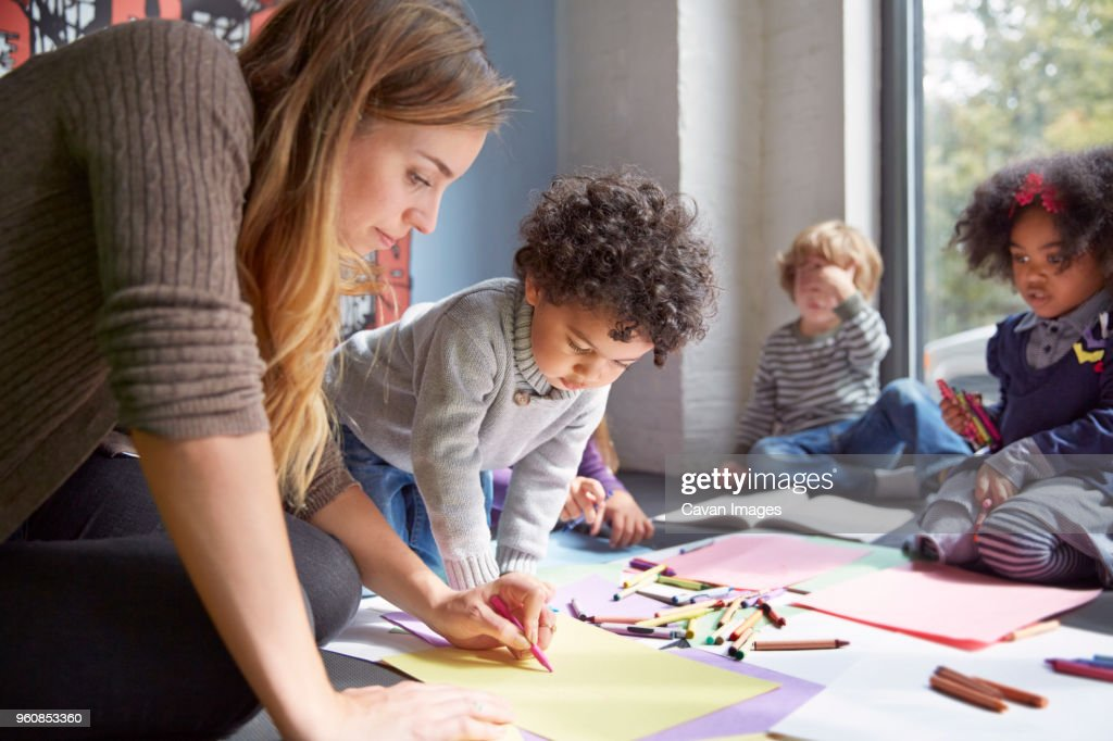 Teacher drawing with students on floor at preschool : Stock Photo