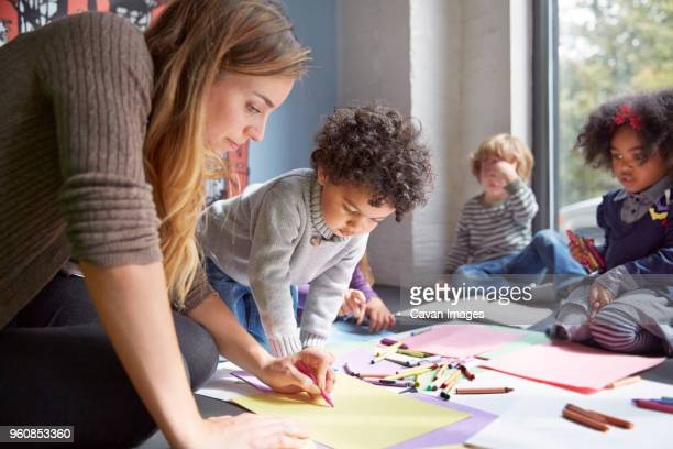 teacher drawing with students on floor at preschool - arti e mestieri foto e immagini stock