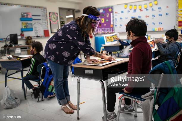 Teacher Elizabeth DeSantis, wearing a mask and face shield, helps a first grader during reading class at Stark Elementary School on September 16,...