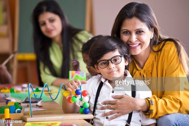 teacher embracing preschool boy - one parent stock pictures, royalty-free photos & images
