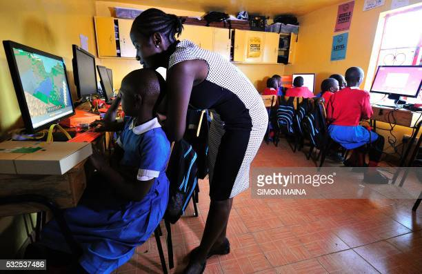 Teacher Emily Monje shows pupils of Kibera School for Girls how to use computers at Nairobi on May 19 2016 Kibera School for Girls offers free...