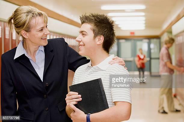Teacher encouraging student in hallway