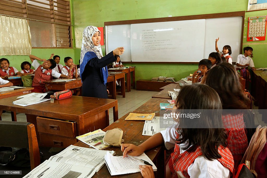 A teacher engages her students during a 5th grade social studies class at their school on February 19, 2013 in Jakarta, Indonesia. A new schools curriculum to take effect in July, 2013 has drawn criticism for its plans to drop science and english classes to provide more time for social and religious education, at a time when Indonesian students are falling behind other countries in the region in Science and Math.