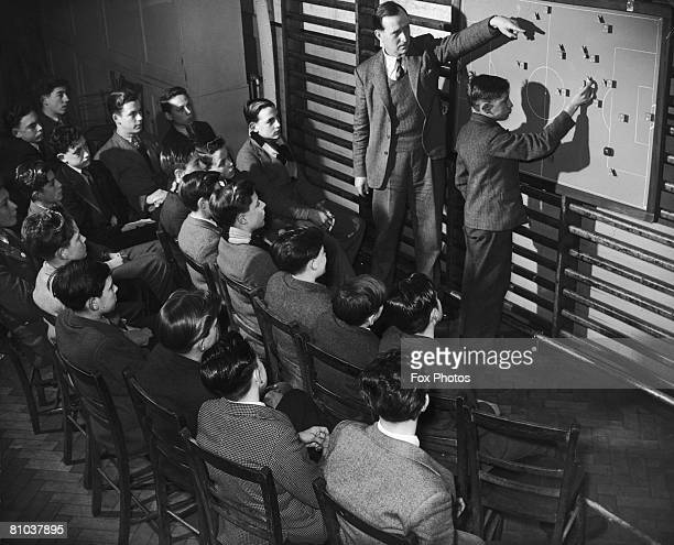 Teacher Eric Ross uses a magnetic football pitch diagram of his own invention to demonstrate tactics to a group of boys from the first and second...