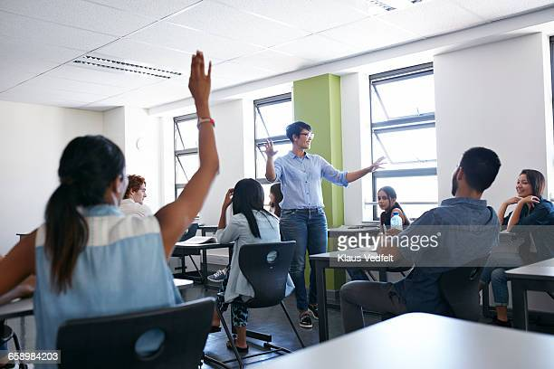 Teacher explaing to class,student with raised hand