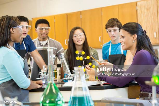 Teacher explaining chemistry model to students