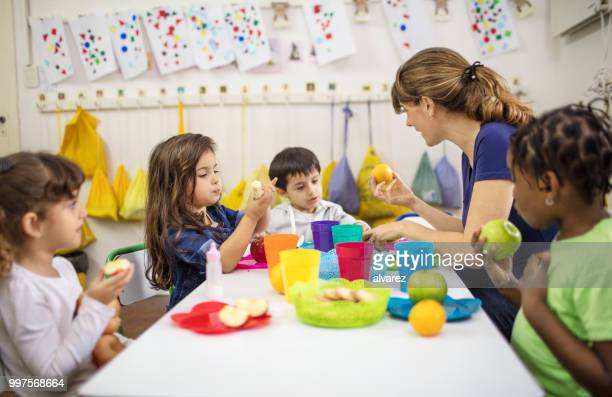 teacher explaining fruits to students in classroom - preschool student stock pictures, royalty-free photos & images