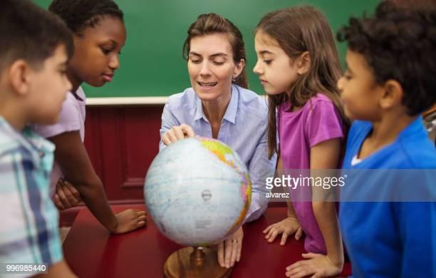 profesor explicando el mundo a los estudiantes en el aula - entrenar fotografías e imágenes de stock