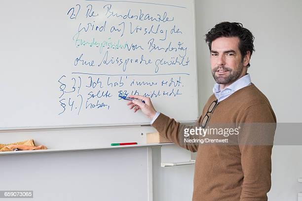 Teacher explaining on whiteboard School, Bavaria, Germany