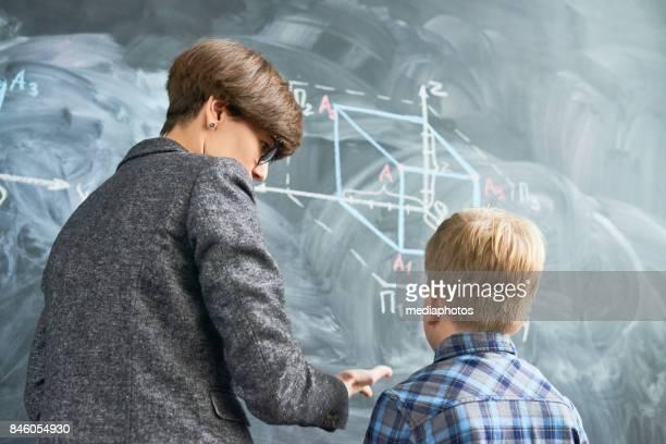 profesor explicando sketch al alumno en el pizarrón - geometria fotografías e imágenes de stock