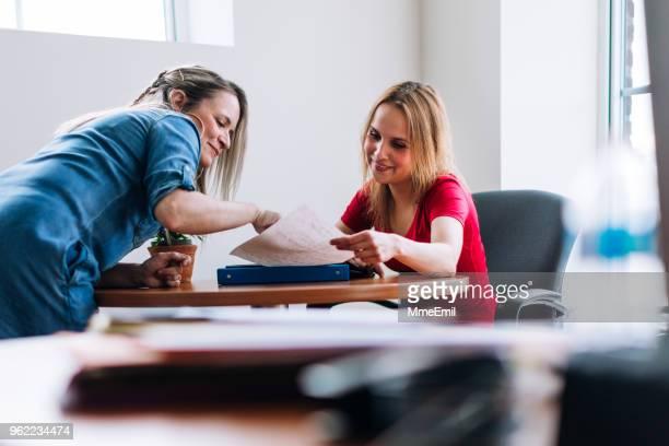 een leraar op een volwassen student iets uit te leggen - maatschappelijk werker stockfoto's en -beelden