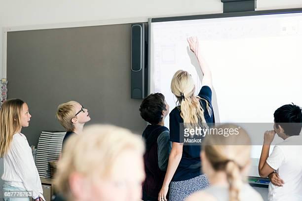 Teacher explaining students on whiteboard in classroom