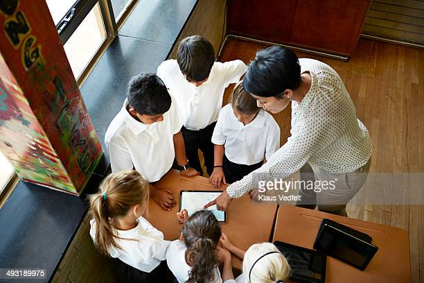 Teacher explaining to students over tablet