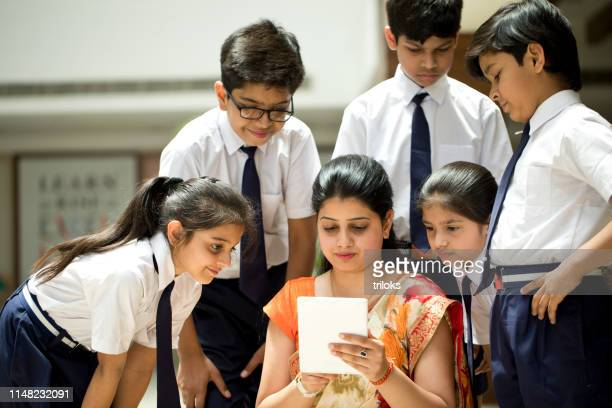 teacher explaining to students using digital tablet - indian ethnicity stock pictures, royalty-free photos & images