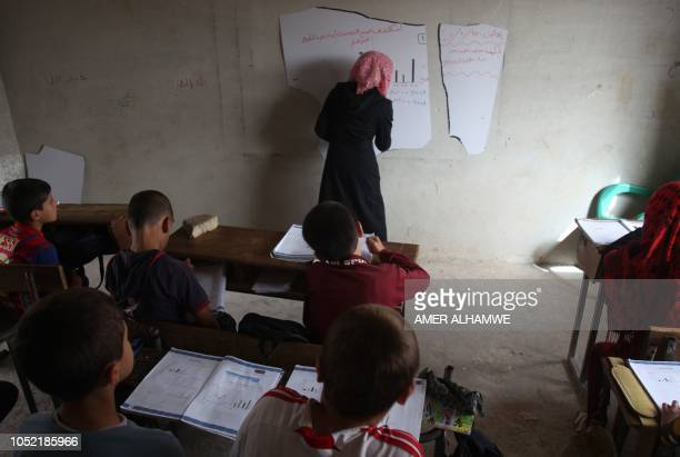 A teacher explains a lesson to her pupils at a school in the city of Harim in the rebelheld northern countryside of Syria's Idlib province on October...
