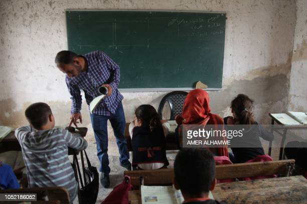 A teacher explains a lesson to his pupils at a school in the city of Harim in the rebelheld northern countryside of Syria's Idlib province on October...
