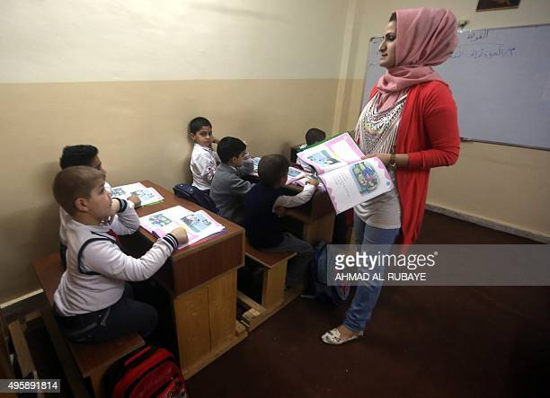 A teacher explains a lesson to students on October 26 2015 at the Mariamana school in the multiethnic northern Iraqi city of Kirkuk where Kurdish...