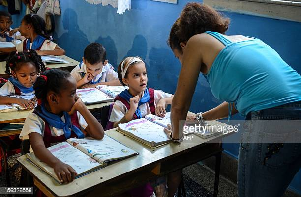 A teacher explains the lesson to her pupils at a school in Havana on November 13 2012 AFP PHOTO/STR