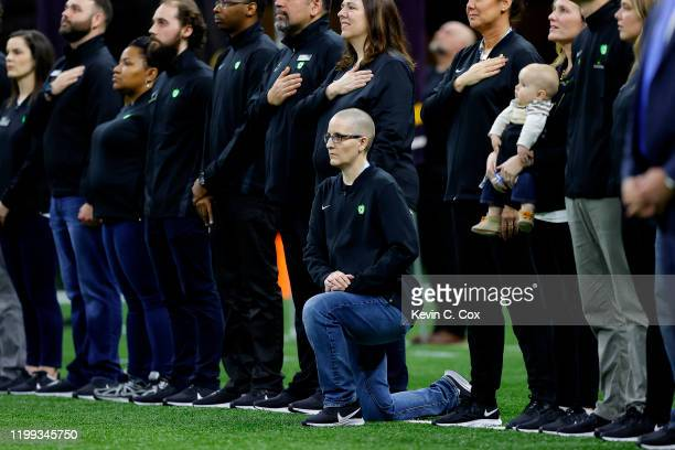 A teacher from the Extra Yard for Teachers charity kneels during the National Anthem prior to the Clemson v LSU game in the College Football Playoff...