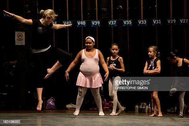 A teacher from the Royal Opera House gives a classic dance class to children from Brazilian dance schools and from shantytowns at the Municipal...