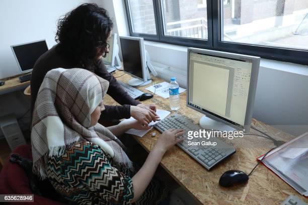A teacher from the women's group FrauenComputerZentrumBerlin eV helps a woman attending a class offering literacy and basic computer and Internet...