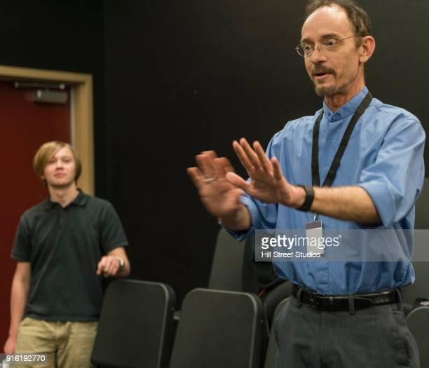 teacher gesturing in theater class - adult film stock-fotos und bilder