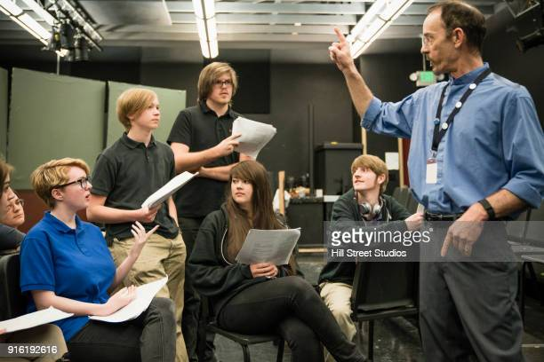 teacher gesturing to students in theater class - acting stock pictures, royalty-free photos & images