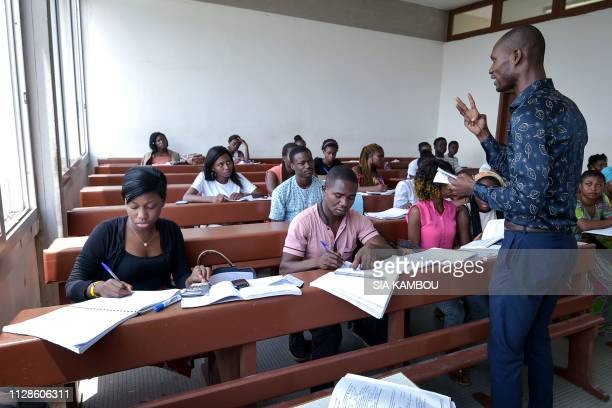 A teacher gives a lesson to students at Felix HouphouetBoigny university in Abidjan as classes start again on March 4 2019 after 6 weeks of strike by...
