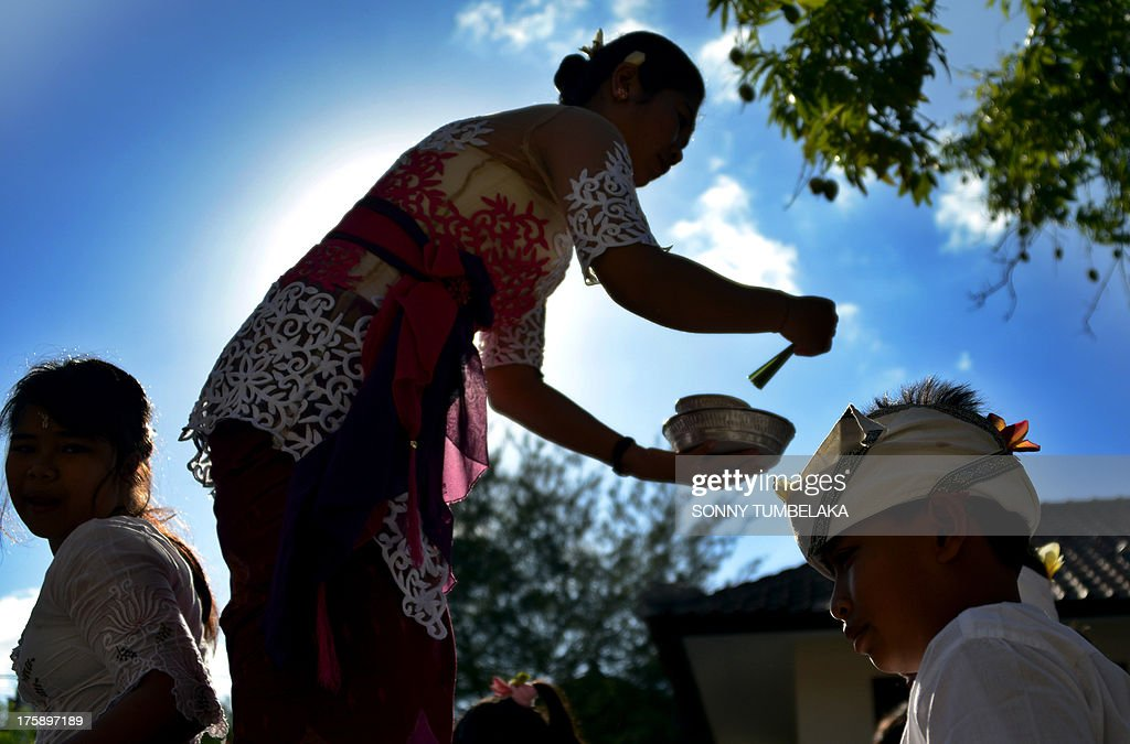 A teacher gives holy water to students during the Hindu Saraswati holy day at a school in Denpasar on Bali island on August 10, 2013. Hindu devotees in Bali celebrated Saraswati day - the day to worship God in his manifestation as the master of all knowledge.