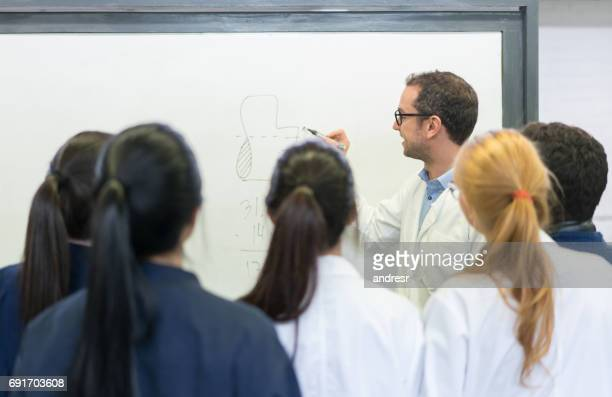 Teacher giving a class to a group of engineering students