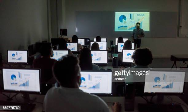 Teacher giving a lecture at the IT classroom to a group of students