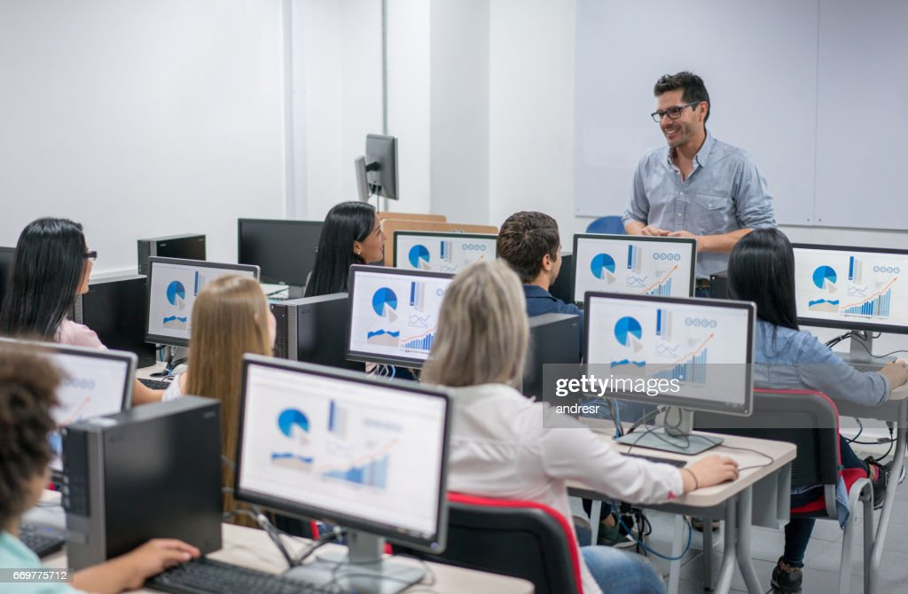Teacher giving an IT class at school to a group of students : Stock Photo