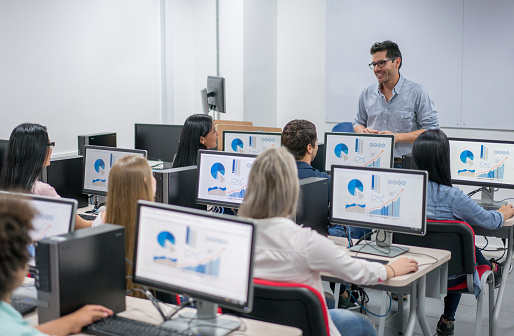 Teacher giving an IT class at school to a group of students 669775712