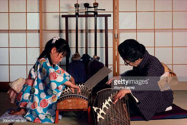 teacher giving girl (9-11) koto lesson - traditional musician stock photos and pictures