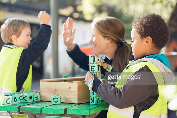 Teacher giving high-five to student while boy arranging blocks at table