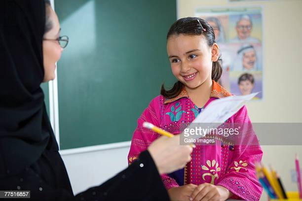 Teacher Giving Homework to Student. Dubai, United Arab Emirates
