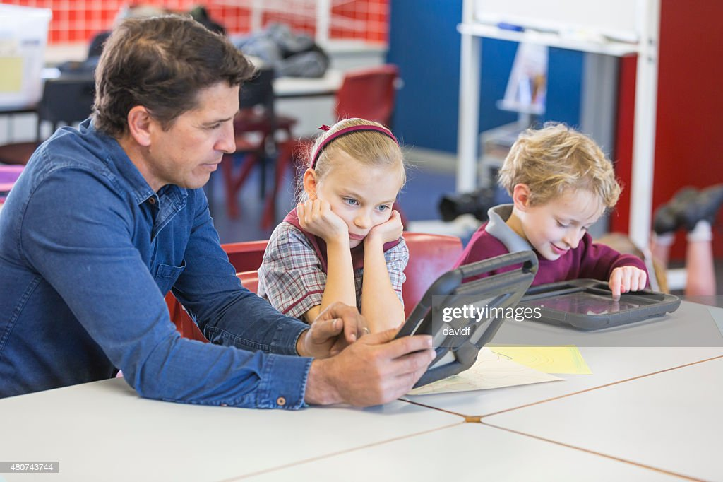 Teacher Giving Lesson Using a Tablet Computer in the Classroom : Stock Photo