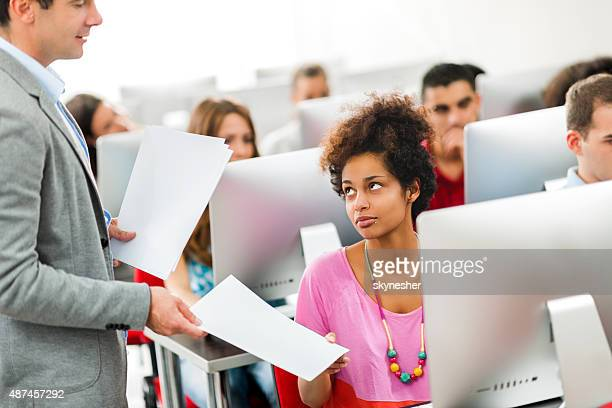 Teacher giving test results to students at computer class.
