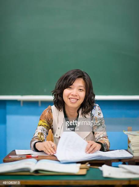Teacher grading papers in classroom