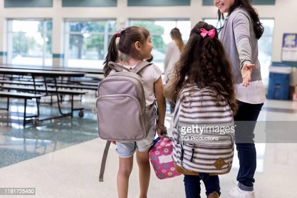 insegnante guida ragazze di età elementare che indossano zaini in mensa - maestra foto e immagini stock