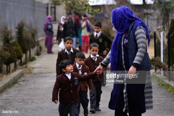 Teacher guiding students towards their classrooms on the first day of school in sopore some 55 kilometers from Srinagar the summer capital of Indian...