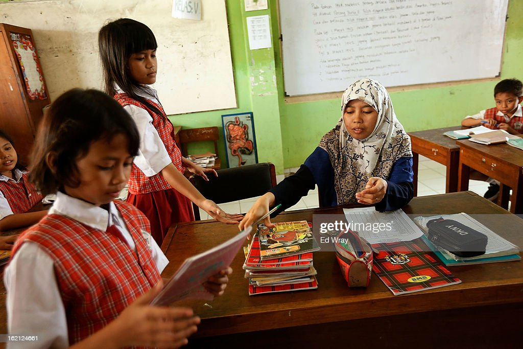 A teacher hands back composition books to 5th grade students at their school on February 19, 2013 in Jakarta, Indonesia. A new schools curriculum to take effect in July, 2013 has drawn criticism for its plans to drop science and english classes to provide more time for social and religious education, at a time when Indonesian students are falling behind other countries in the region in Science and Math.