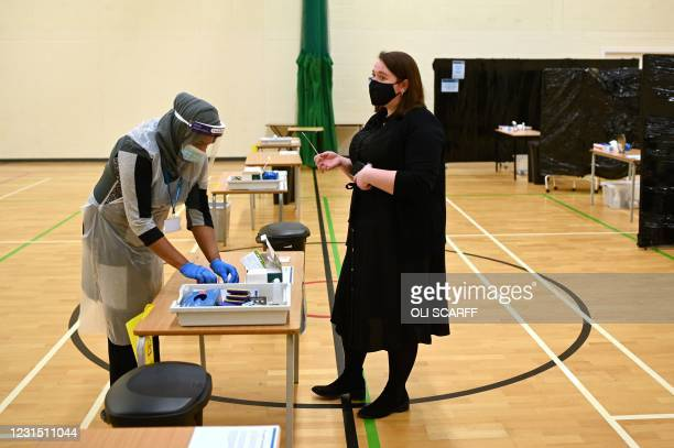 Teacher hands over a Covid-19 lateral flow test to another staff member in the sports hall of Park Lane Academy in Halifax, northwest England on...