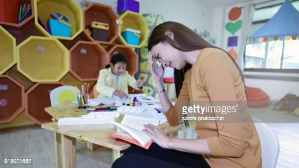Teacher having Stress symptoms on learning  in an international preschool.teacher ,education, kid and primary school concept .